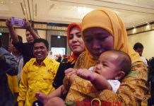 TANTANGAN ASUH GENERASI: Mensos Khofifah Indar Parawansa menggendong bayi salah seorang ibu peserta seminar nasional yang digelar Pengurus Gerakan Perempuan MKGR di Surabaya, Jumat (22/12). | Foto: Barometerjatim.com/ABDILLAH HR