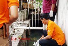 MAYAT TANPA IDENTITAS: Petugas mengidentifikasi mayat yang ditemukan tengkurap di selokan Jalan Ngagel Jaya Selatan II, Surabaya, Senin (1/1). | Foto: Barometerjatim.com/ENEF MADURY