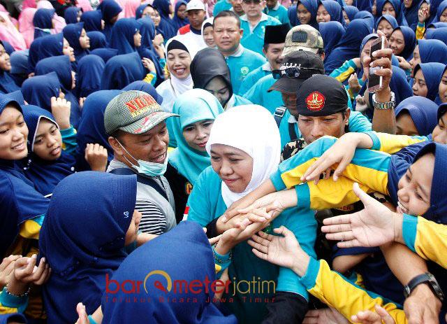 BEREBUT SALAMAN: Dengan kawalan Banser, Khofifah Indar Parawansa meladeni dengan ramah serbuan massa jalan sehat untuk bersalaman.   Foto: Barometerjatim.com/MARIJAN AP
