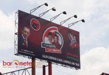 BELUM DITURUNKAN: Meski menyalahi aturan pemasangan APK, billboard paslon ini masih berdiri kokoh dan tak kunjung diturunkan Bawaslu. | Foto: Barometerjatim.com/ABDILLAH HR