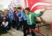 'GENDONG' BOLA RAKSASA: Menpora Imam Nahrawi berpose seolah menggendong bola raksasa di sela pelantikan KNPI Jatim, Sabtu (21/7). | Foto: Barometerjatim.com/NANTHA LINTANG