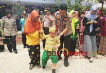 POLISI PEDULI: AKBP Feby DP Hutagalung menuntun Rizky menggunakan kaki palsunya di halaman PAUD Raudlatul Mahmudah Lamongan. | Foto: Barometerjatim.com/HAMIM ANWAR