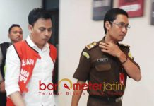 KORUPSI UANG NASABAH: Kasna Gustiansah (kiri) menuju mobil tahanan Kejari Surabaya lantaran diduga melakukan korupsi uang nasabah. | Barometerjatim.com/ABDILLAH HR
