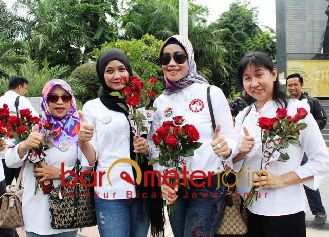 MAWAR MERAH: Perempuan dari TKD membawa mawar merah untuk pengguna jalan di Jalan Raya Darmo, Surabaya, Minggu (2/12).   Foto: Barometerjatim.com/ROY HASIBUAN
